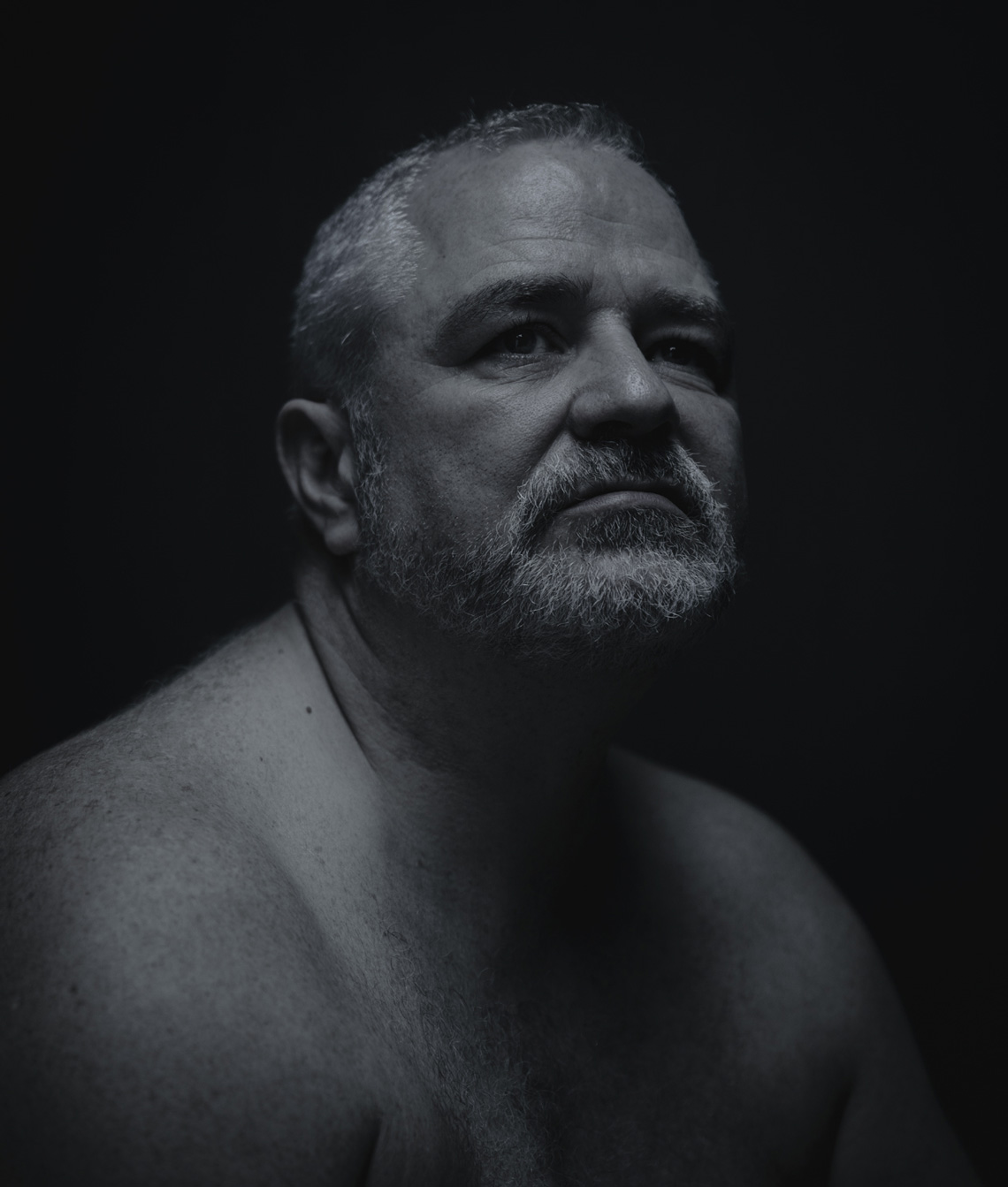 Dramatic portrait of  man with bare shoulders on dark background by Lenka Rayn H.