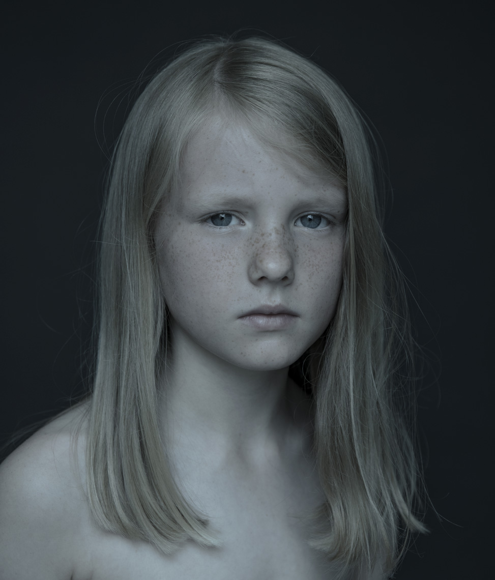 Portrait of young girl with blond hair on dark background by Lenka Rayn H.